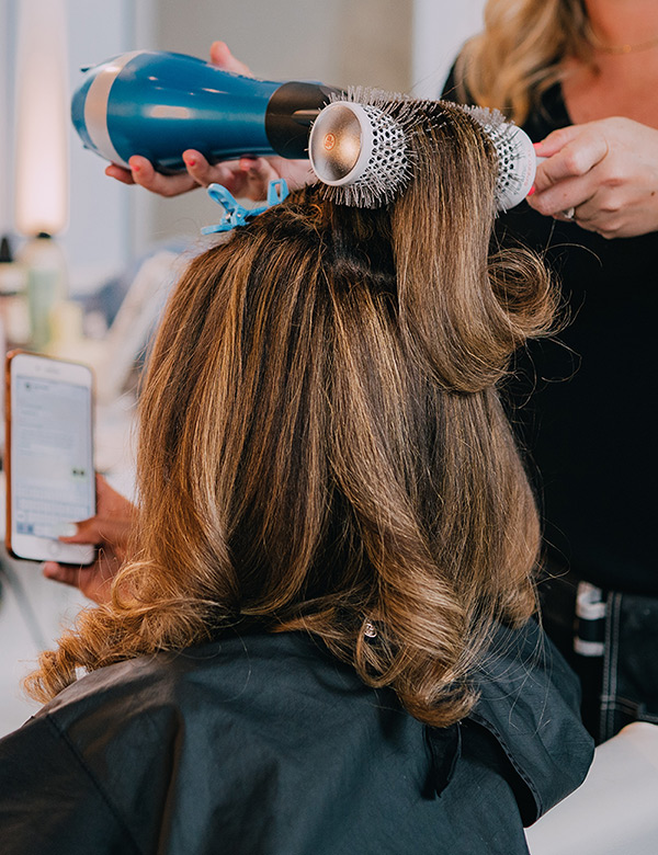 Stylist drying a clients hair with a round brush