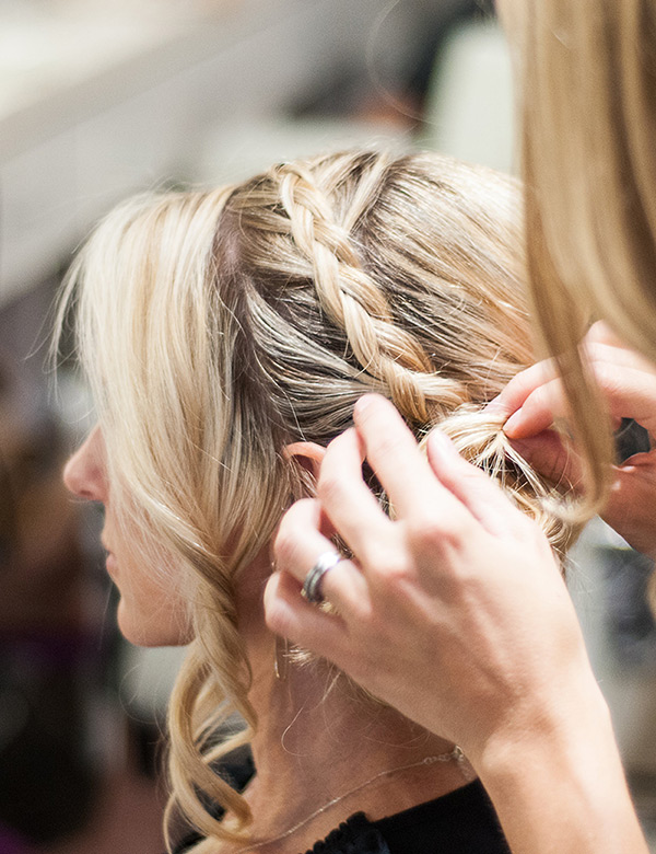 Stylist putting finishing touches on an updo