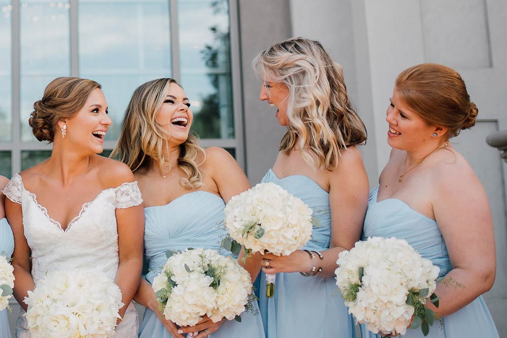 Bride and Bridesmaids on wedding day pose and laugh