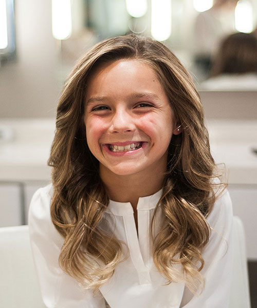 Young girl smiles with finished blowout