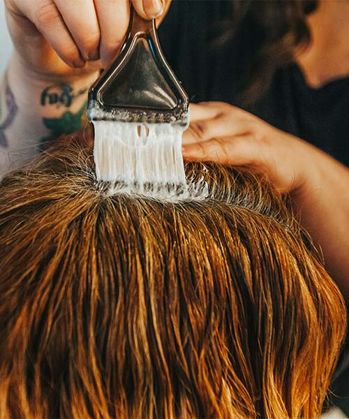 Stylist touches up clients roots
